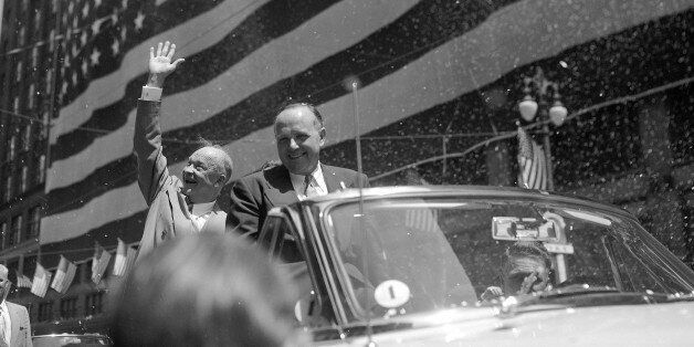 Gen. Dwight D. Eisenhower waves to confetti-tossing crowds lining the parade route to Detroit's City Hall, June 14, 1952, whe