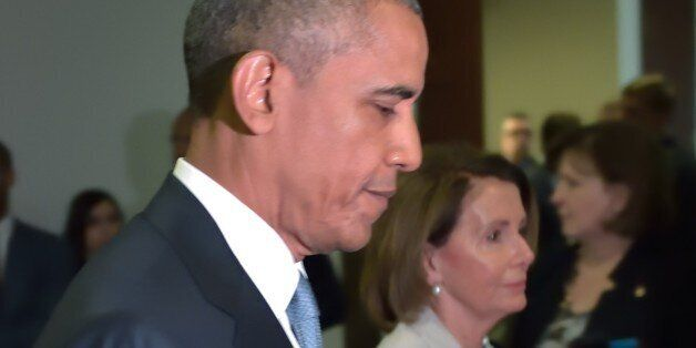 US President Barack Obama and House Minority Leader Nancy Pelosi walk through a hallway after meeting with House Democrats at