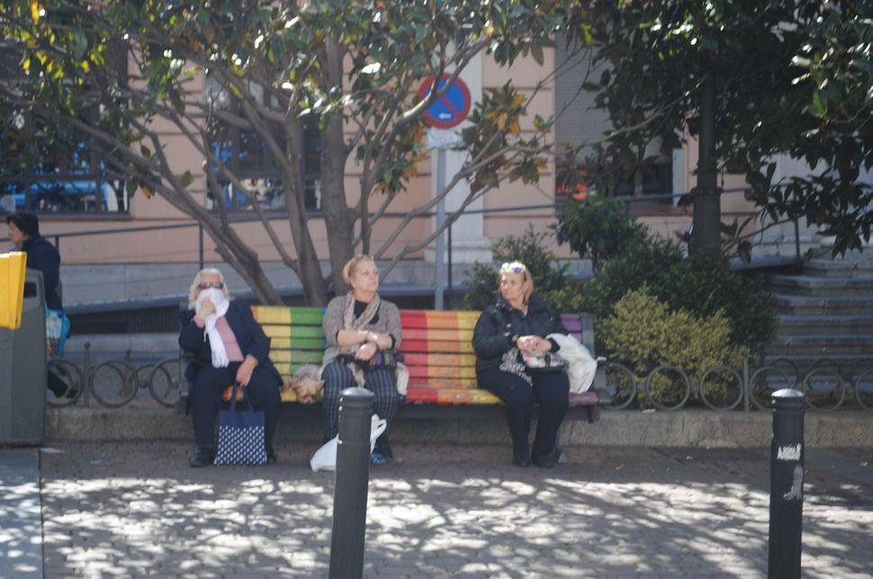 Um dia antes de o governo espanhol limitar circulação, mulheres descansam em praça pública.