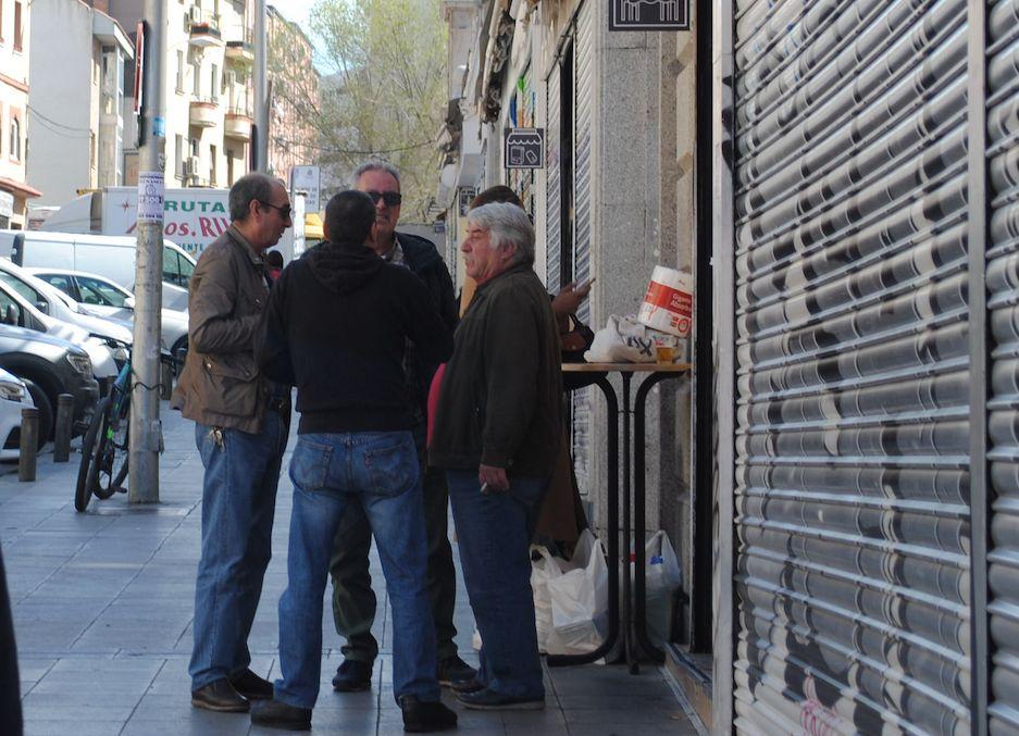 Unos hombres charlan tomando algo en la puerta del mercado de