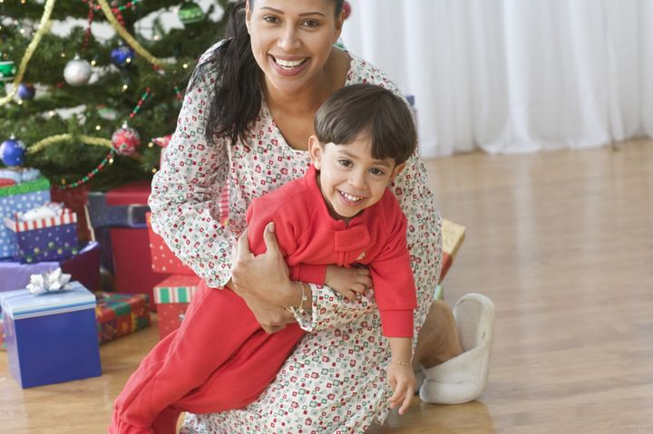 Mom sitting in front of Christmas tree holding her young son