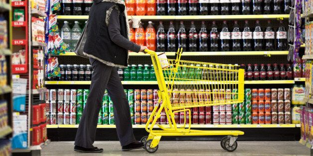 Customer Wendy Rosen pushes a shopping cart past a display of soft drinks at a Dollar General Corp. store in Saddle Brook, Ne