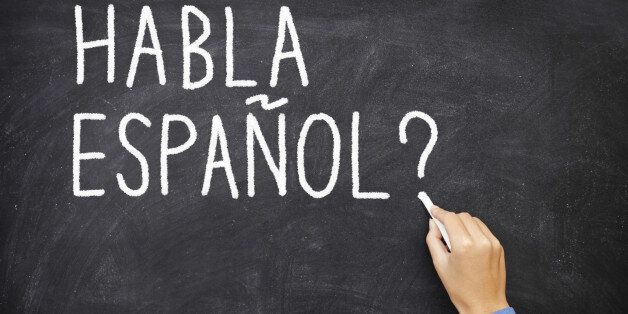 Spanish language learning concept image. Teacher or student writing 'habla espanol' on blackboard during spanish language cou
