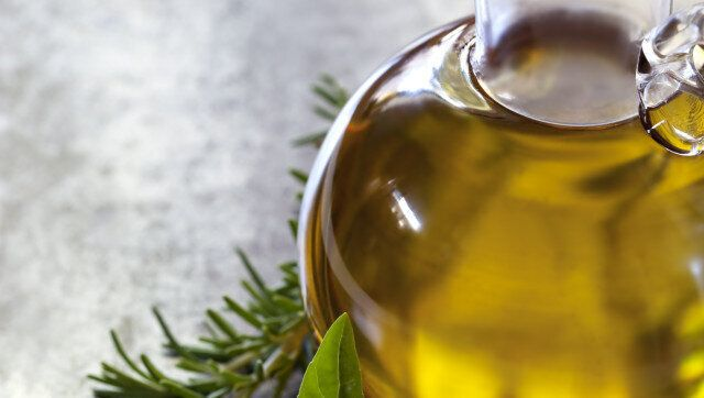 Bottle of olive oil, with fresh basil and rosemary.