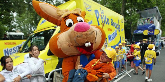 Castres, FRANCE: A person dressed up as Nesquick character holds a child as the advertising caravan passes by during the 12th stage of the 94th Tour de France cycling race between Montpellier and Castres, 20 July 2007. Nesquick is the official supplier since 2006. Tour de France is the opportunity to promote sponsor's products, with more than 15 million spectators each year and over a hundred million television viewers all around the world.   AFP PHOTO / JOE KLAMAR (Photo credit should read JOE KLAMAR/AFP/Getty Images)