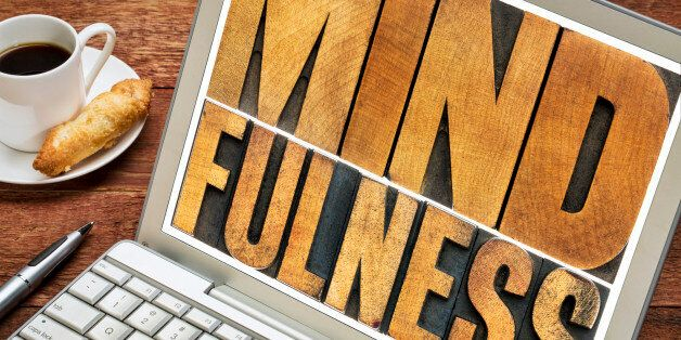 mindfulness word typography - isolated text in letterpress wood type on a laptop screen - spiritual concept