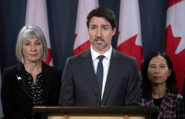 Minister of Health Patty Hajdu and Chief Medical Officer Theresa Tam look on as Justin Trudeau responds...