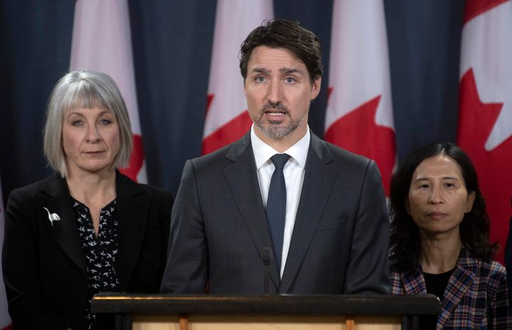 Minister of Health Patty Hajdu and Chief Medical Officer Theresa Tam look on as Justin Trudeau responds to a question in Ottawa on March 11, 2020.
