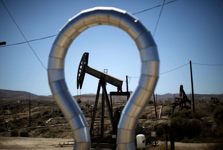 Pump jacks swing in the Midway Sunset oilfield in California, near a large shale formation.