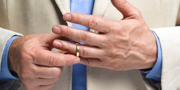 Divorced man taking off wedding ring