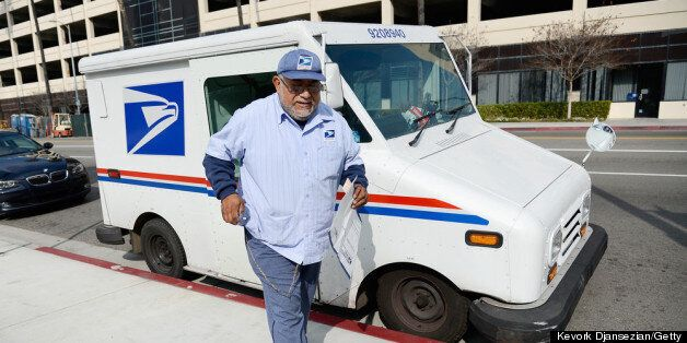 LOS ANGELES, CA - FEBRUARY 06:  U.S. Postal Service employee Arturo Lugo delivers an Express Mail package during his morning