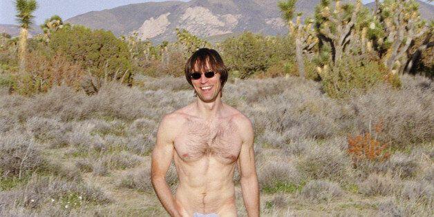 Naked man walking outdoors