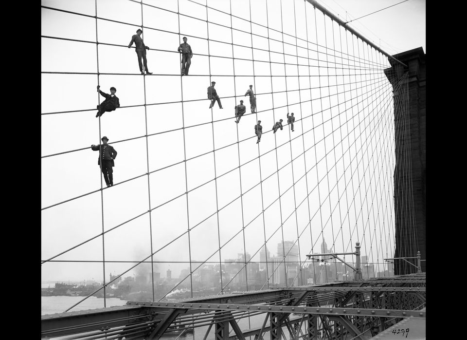 In this Oct. 7, 1914 photo provided by the New York City Municipal Archives, painters are suspended from wires on the Brookly