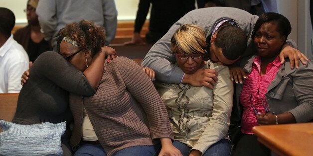 The family/supporters of Dushawn Taylor-Gennis, including his mother Genneane Gennis, seated second from right, react at the