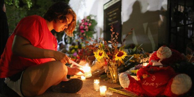 CHARLESTON, SC - JUNE 18: A woman lights candles for the nine victims of last night's shooting at the historic Emanuel African Methodist Episcopal Church June 18, 2015 in Charleston, South Carolina. Dylann Storm Roof, 21, of Lexington, South Carolina, who allegedly attended a prayer meeting at the church for an hour before opening fire and killing three men and six women, was arrested today. Among the dead is the Rev. Clementa Pinckney, a state senator and a pastor at Emanuel AME, the oldest black congregation in America south of Baltimore, according to the National Park Service. (Photo by Chip Somodevilla/Getty Images)