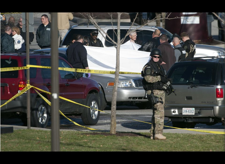 Police officials examine the body of a police officer shot to death in a parking lot on the campus of Virginia Tech, Thursday