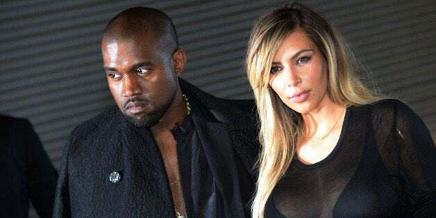 US musician Kanye West and partner Kim Kardashian pose prior to Givenchy 2014 Spring/Summer ready-to-wear collection fashion