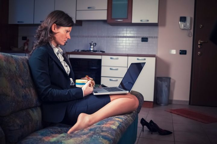 Businesswoman working at home with a laptop sitting on the sofa.