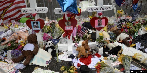 Items and crosses decorate a makeshift memorial April 20, 2013 on Boylston Street, near the scene of Boston Marathon explosions as people get back to the normal life the morning after after the capture of the second of two suspects wanted in the Boston Marathon bombings. Thousands of heavily armed police staged an intense manhunt Friday for a Chechen teenager suspected in the Boston marathon bombings with his brother, who was killed in a shootout. Dzhokhar Tsarnaev, 19, defied the massive force after his 26-year-old brother Tamerlan was shot and suffered critical injuries from explosives believed to have been strapped to his body. AFP PHOTO / TIMOTHY A. CLARY (Photo credit should read TIMOTHY A. CLARY/AFP/Getty Images)