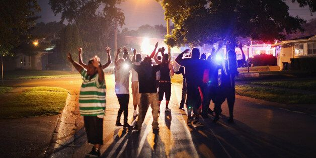 FERGUSON, MO - AUGUST 11:  With their hands raised, residents gather at a police line as the neighborhood is locked down foll