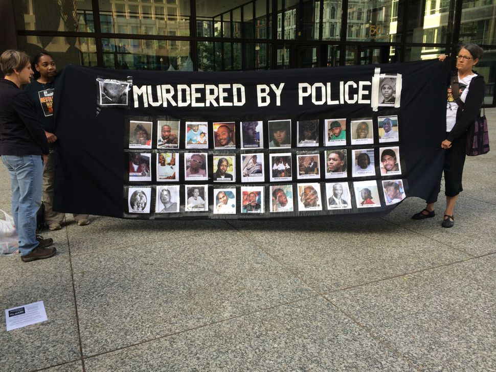The Stop Mass Incarceration Network hold a banner memorializing victims of police brutality at Chicago's #NMOS vigil, August