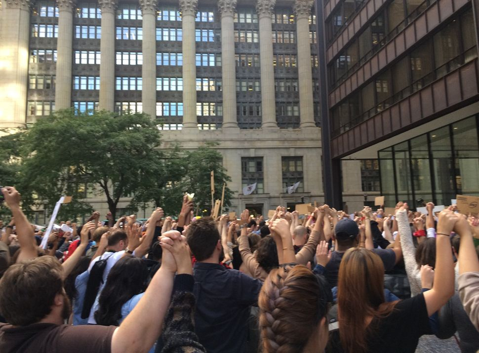 The crowd locks raised hands during four minutes of silence at the #NMOS vigil in Chicago on August 14, 2014.