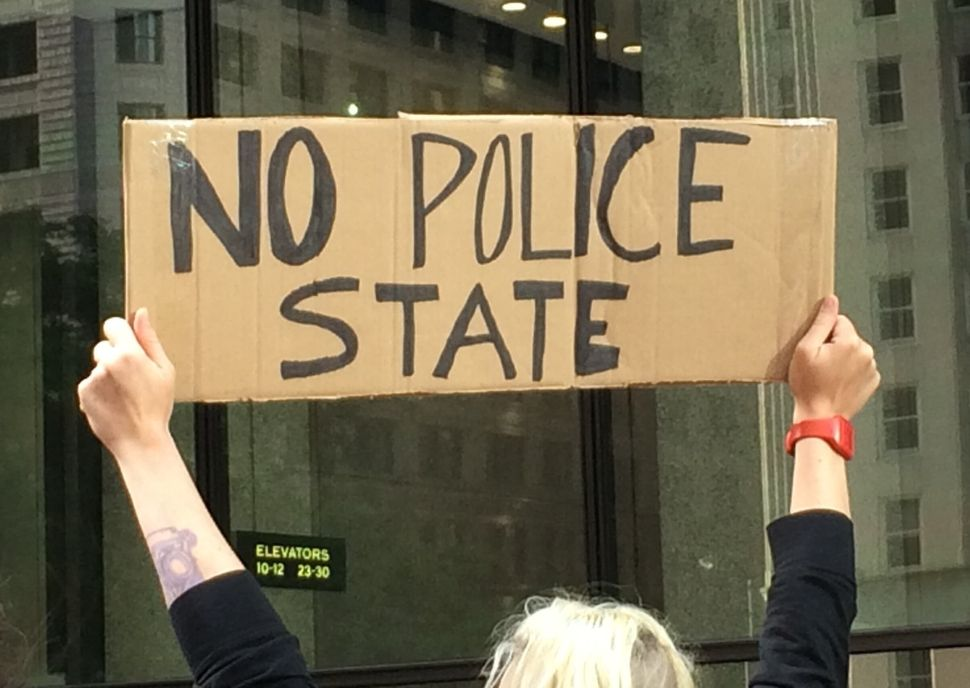 "A woman holds a ""No Police State"" sign at Chicago's #NMOS vigil on August 14, 2014."