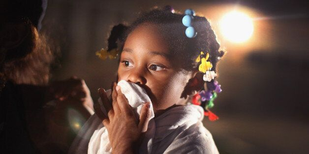 FERGUSON, MO - AUGUST 11:  A child uses a rag to shield her face from tear gas being fired by police who used it to force pro