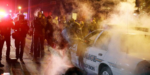 A police officer approach a police vehicle after a protester has thrown a smoke device from the crowd Tuesday, Nov. 25, 2014,