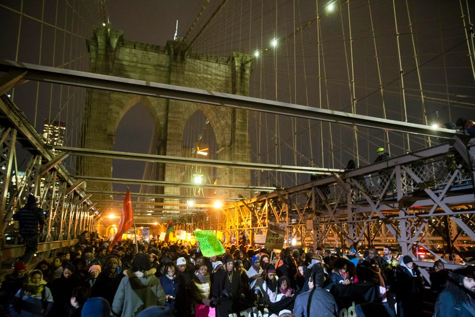 Demonstrators march across the Brooklyn Bridge during a protest against a grand jury's decision not to indict the police offi