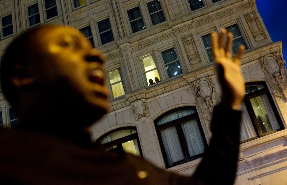 Guests look out of their hotel room as Keith Stephens, of Atlanta, chants with fellow protesters in Atlanta on Thursday durin