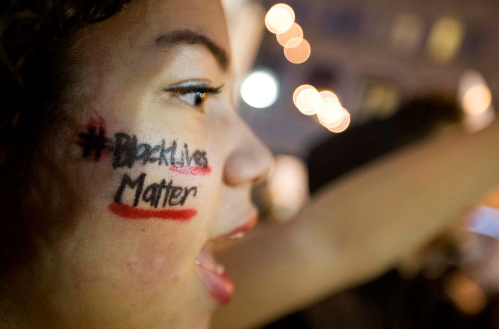 """A message reading """"Black Lives Matter"""" is written across the cheek of Samaria Muhammad as she chants with fellow protesters i"""