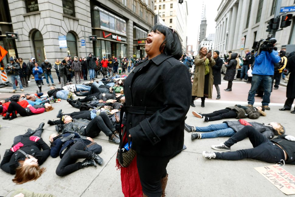 A demonstrator screams as others protest the deaths of two unarmed black men at the hands of white police officers in New Yor