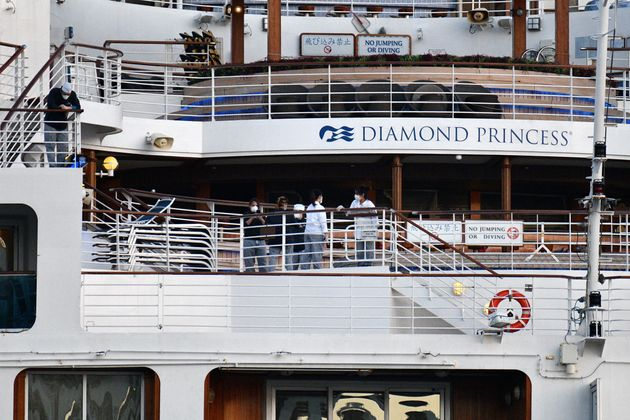 This picture taken on February 24, 2020 shows crew members aboard the Diamond Princess cruise ship at...