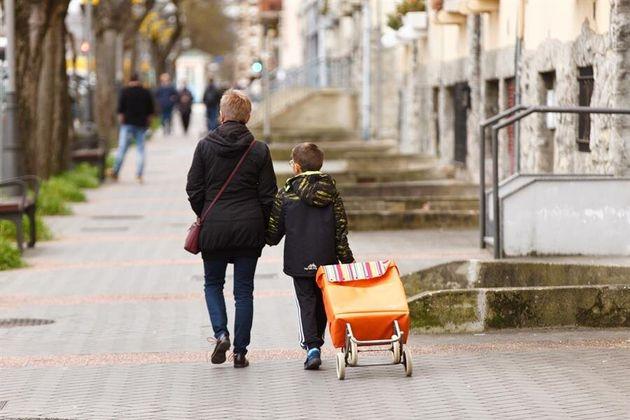 Un escolar acompaña a una mujer a la compra este jueves en