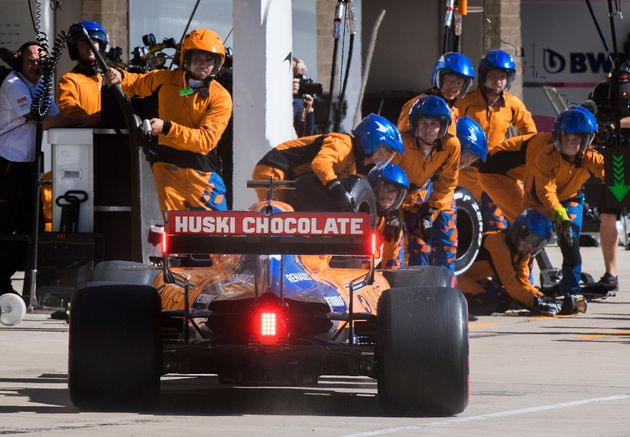 McLaren driver Carlos Sainz, of Spain, enters the pit as the team's crew members watch during the Formula...