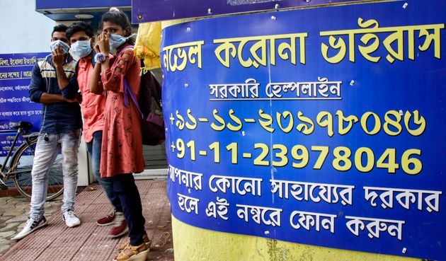 People wearing masks stand next to COVID-19 helpline number displayed on a wall at government run hospital...