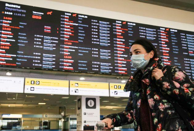 Une jeune femme portant un masque pour se protéger du coronavirus, le 12 mars 2020 dans un aéroport...