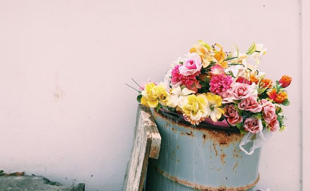 Flower Bouquet In Garbage Can Against Wall