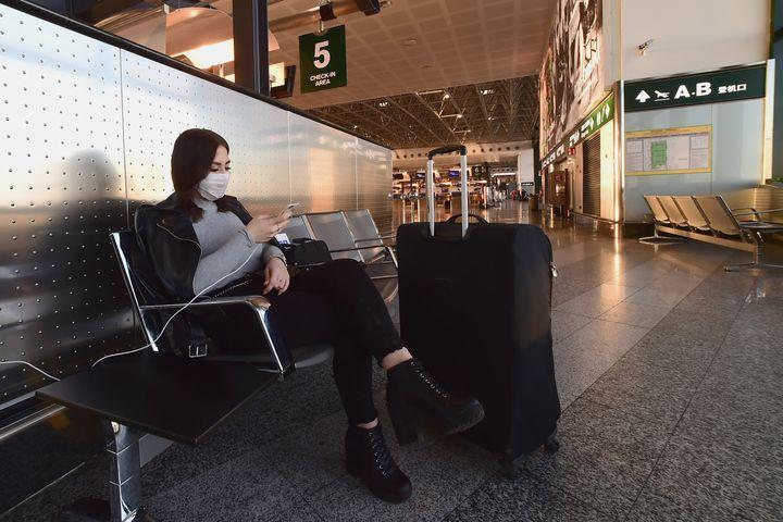 Una mujer espera en el aeropuerto de Malpensa, Milán (Italia).