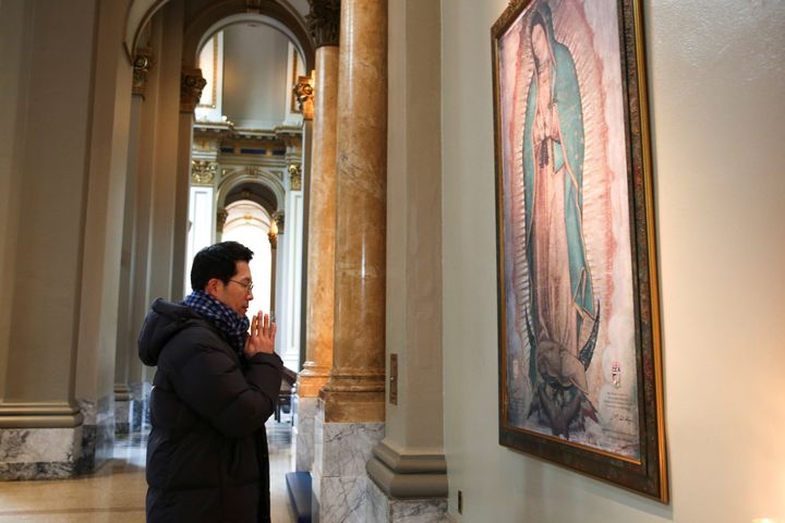 Jun Lee, a Catholic from South Korea, prays during a visit to St. James Cathedral, which is only open for prayer after the Ar