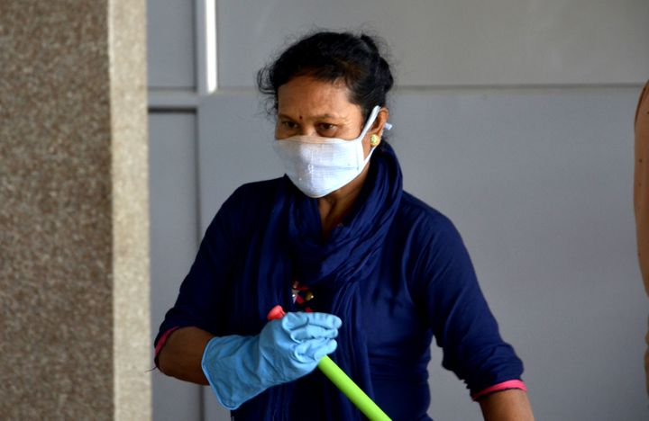 A railway worker wears face mask as a preventive measure against coronavirus, as she cleans the railway station in Guwahati, Assam, India on March 12, 2020.