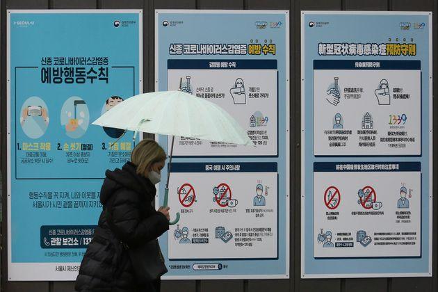 마스크를 쓴 한 시민이 코로나19 포스터 앞을 지나가고 있다. 서울. 2020년