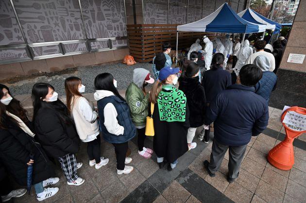 코로나19 집단감염이 발생한 콜센터가 위치한 서울 구로구의 빌딩에 임시로 설치된 시설에서 검사를 받기 위한 대기줄이 형성되어 있다. 2020년