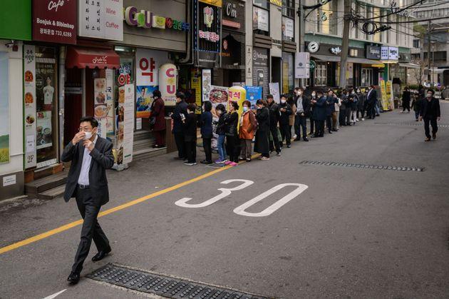 서울의 한 약국 앞에 마스크를 구입하려는 시민들이 길게 줄을 서고 있다. 2020년