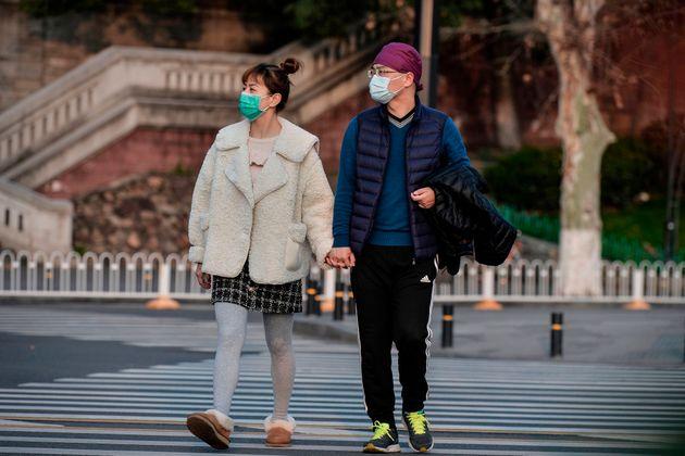 마스크를 착용한 시민들이 거리를 걷고 있다. 우한, 중국. 2020년