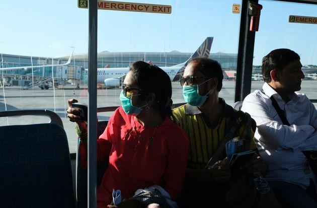 Passengers wearing masks as a precaution against a coronavirus ride a bus at Chhatrapati Shivaji International...