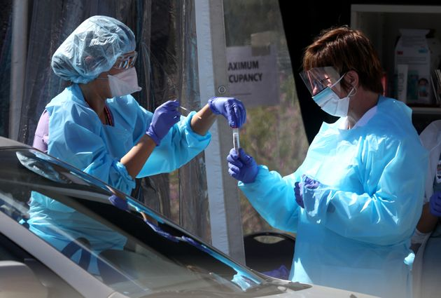 Medical workers receive a sample from a person at a drive-thru COVID-19 testing station in San Francisco...