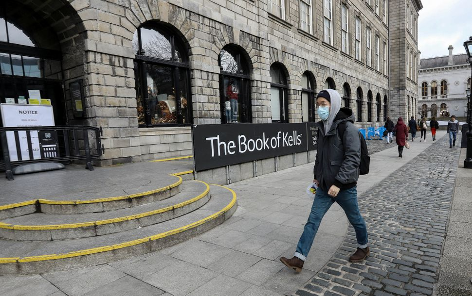 A man in a protective mask walks past the entrance to the Book of Kells building, usually crowded with...