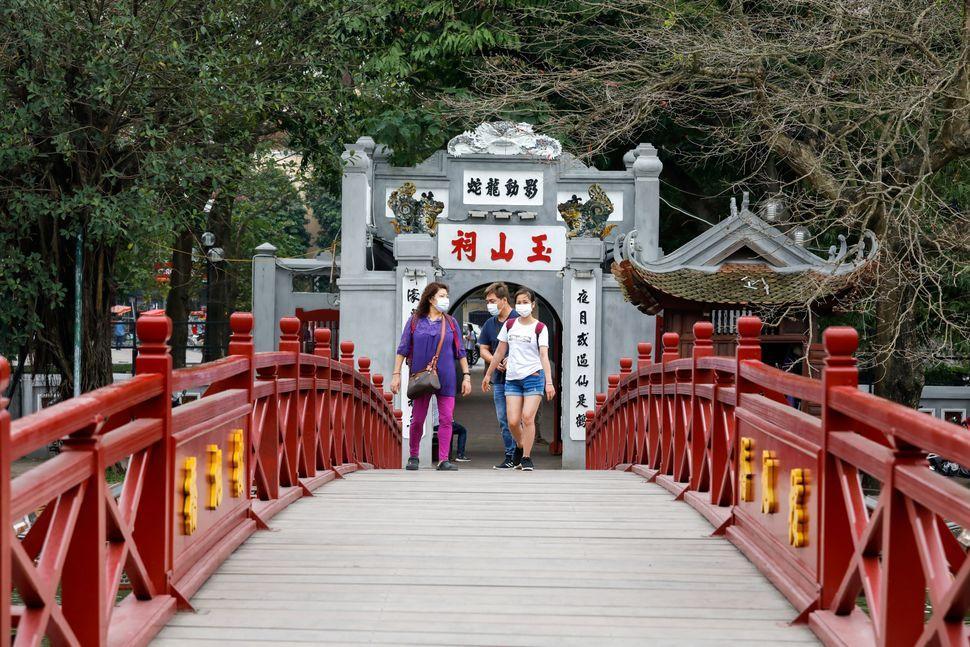 Foreign tourists wear protective masks and walk on the empty The Huc bridge on Hoan Kiem lake in Hanoi,